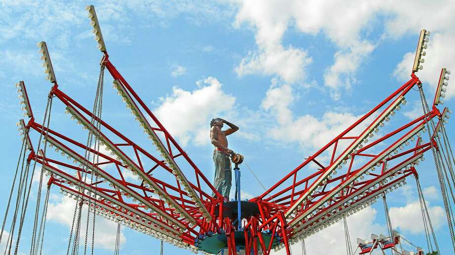 Meriden resident Steven Hubbard wipes the sweat from his brow in this 2012 file photo while setting up the Musical Chairs for the Riverport Festival at Pierson Park in Cromwell. Photo: Catherine Avalone — The Middletown Press  / a