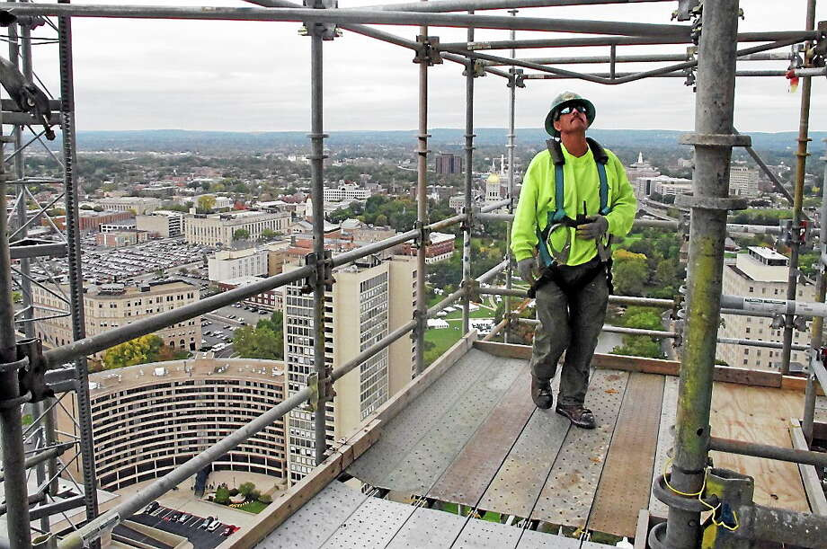 In this Oct. 10, 2013 photo, construction laborer Tom Hajbucki looks up at a co-worker on scaffolding erected outside the Travelers Tower in Hartford, Conn. Photo: AP Photo/Dave Collins  / AP