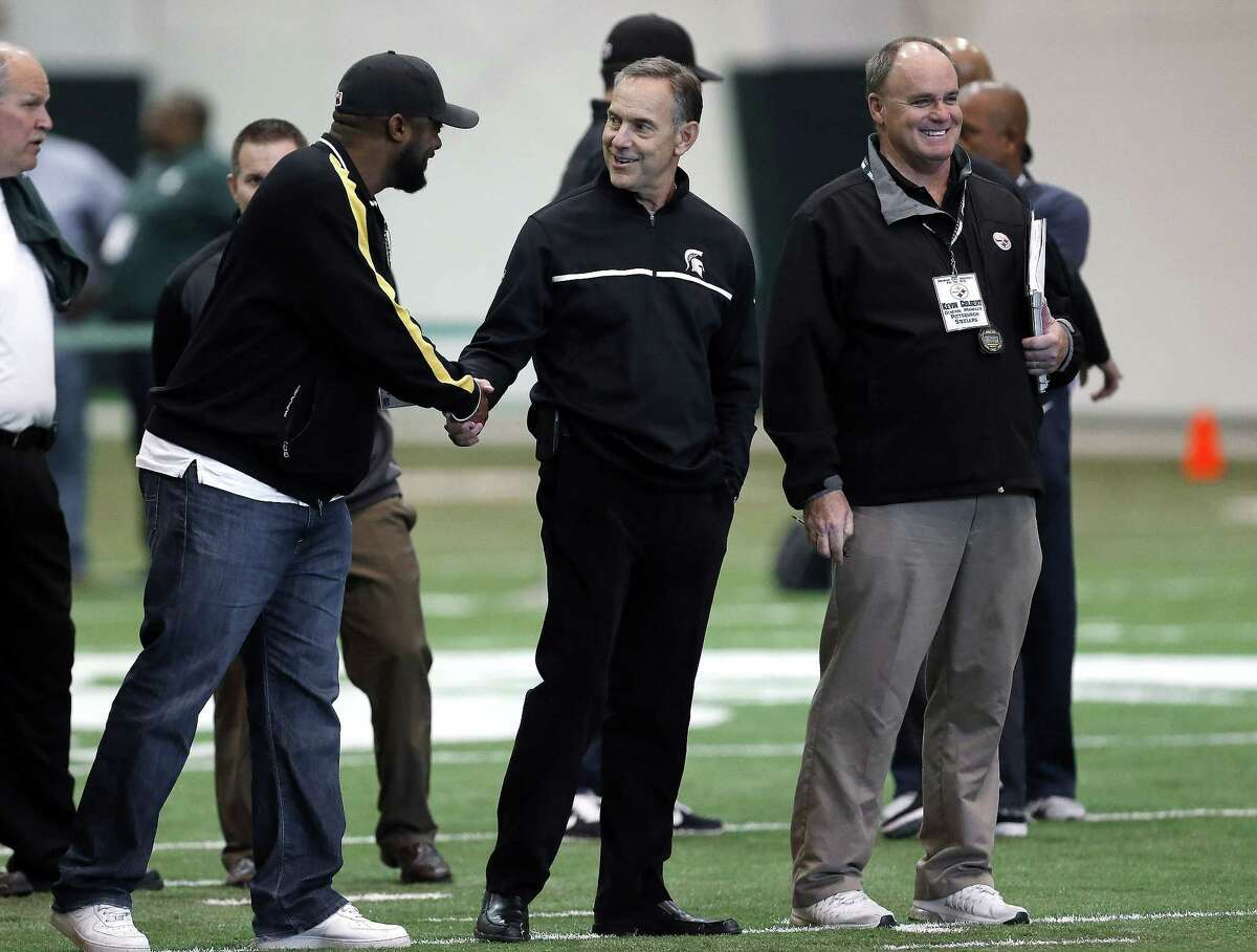 Pittsburgh Steelers head coach Mike Tomlin, left, shakes hands with Michigan State head coach Mark Dantonio, center, as Steelers general manager Kevin Colbert looks on during a pro day on March 18 in East Lansing, Mich.