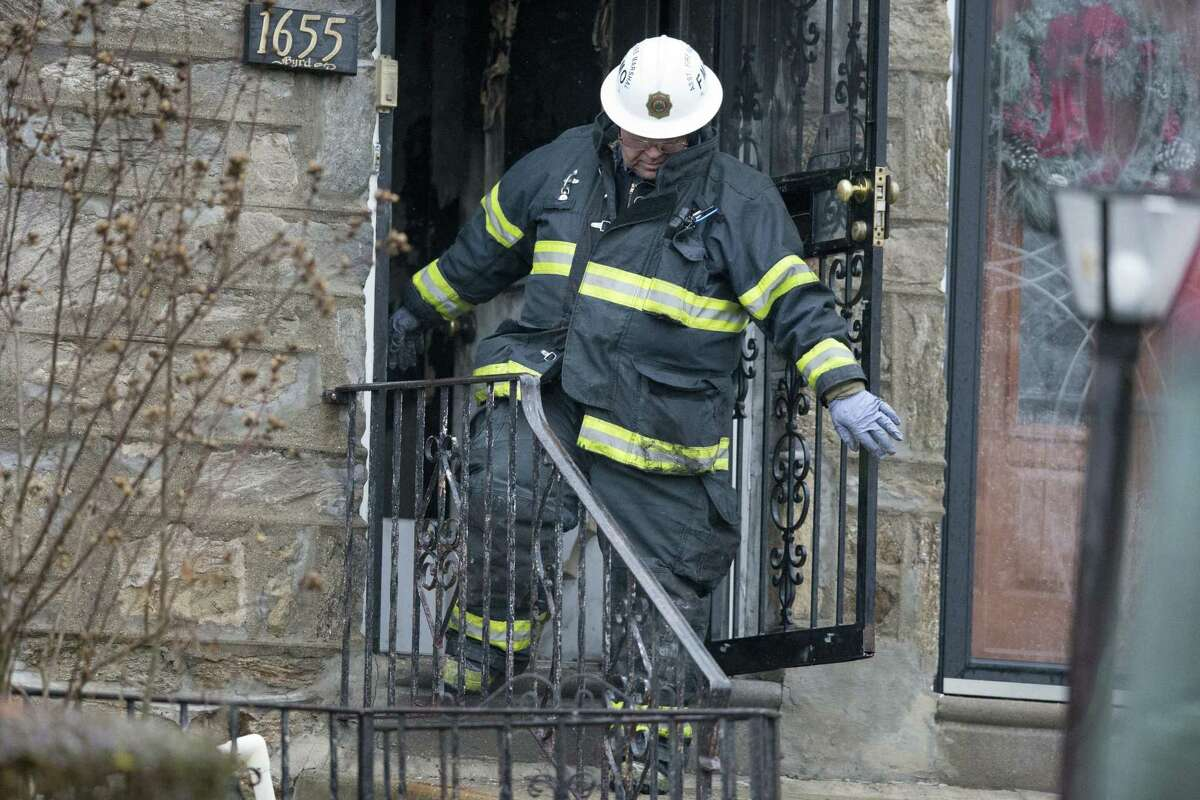 A fire marshal exits a burned out home in the aftermath of a fatal fire Tuesday, Dec. 9, 2014, in Philadelphia. A firefighter was trapped in the basement of the burning row home early Tuesday, becoming the first female member of the Philadelphia Fire Department to die in the line of duty, officials said. The 11-year veteran was part of the first company deployed to a fire in the basement of the home in the city's West Oak Lane neighborhood at about 3 a.m. Tuesday, fire commissioner Derrick Sawyer said.