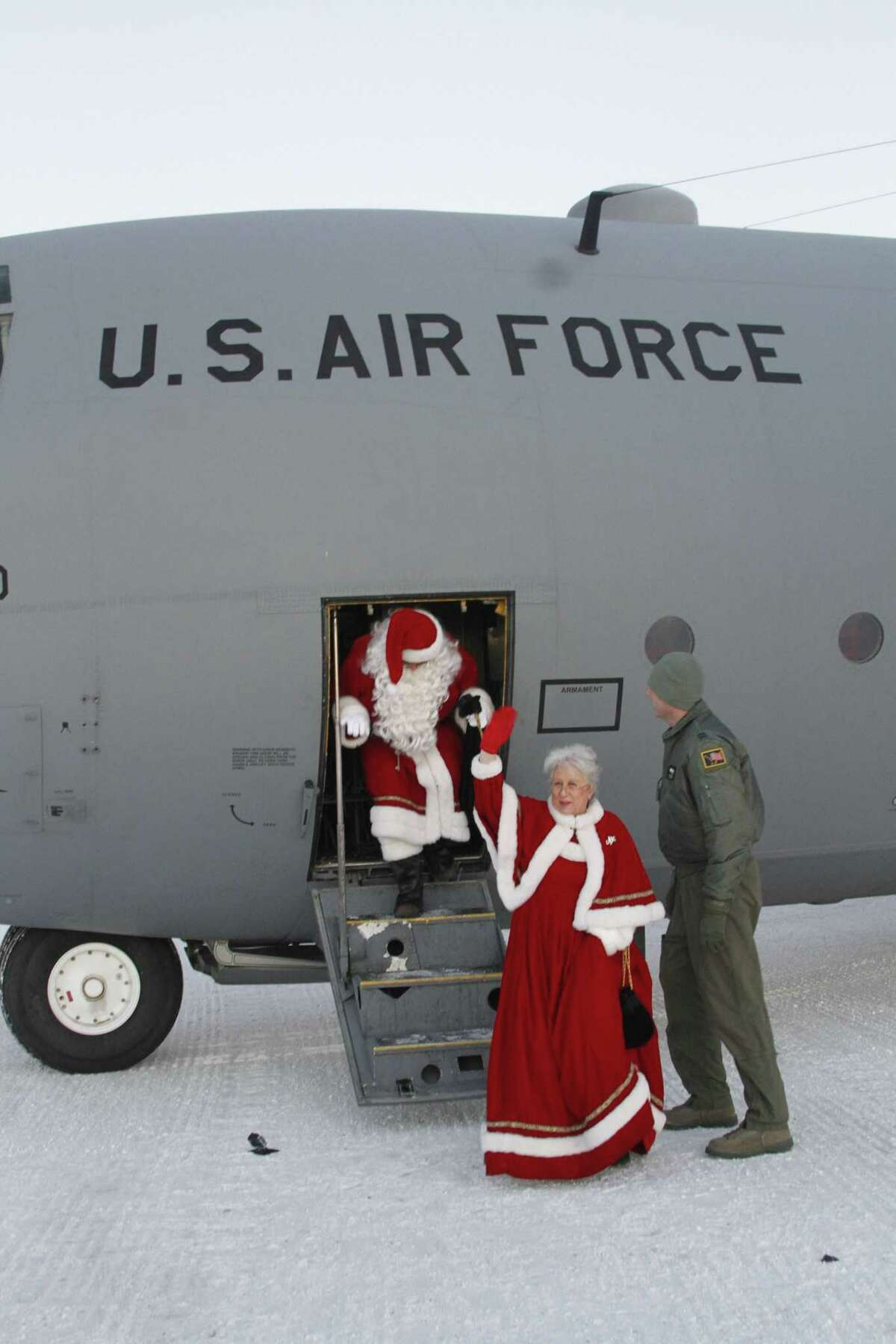 This photo taken Dec. 6, 2014, shows Santa and Mrs. Claus getting off a C130 military transport plane in Shishmaref, Alaska. The Alaska National Guard provided transport for the good Samaritan program Operation Santa, which took gifts and schools supplies to about 300 children in the Inupiat Eskimo community. (AP Photo/Mark Thiessen)