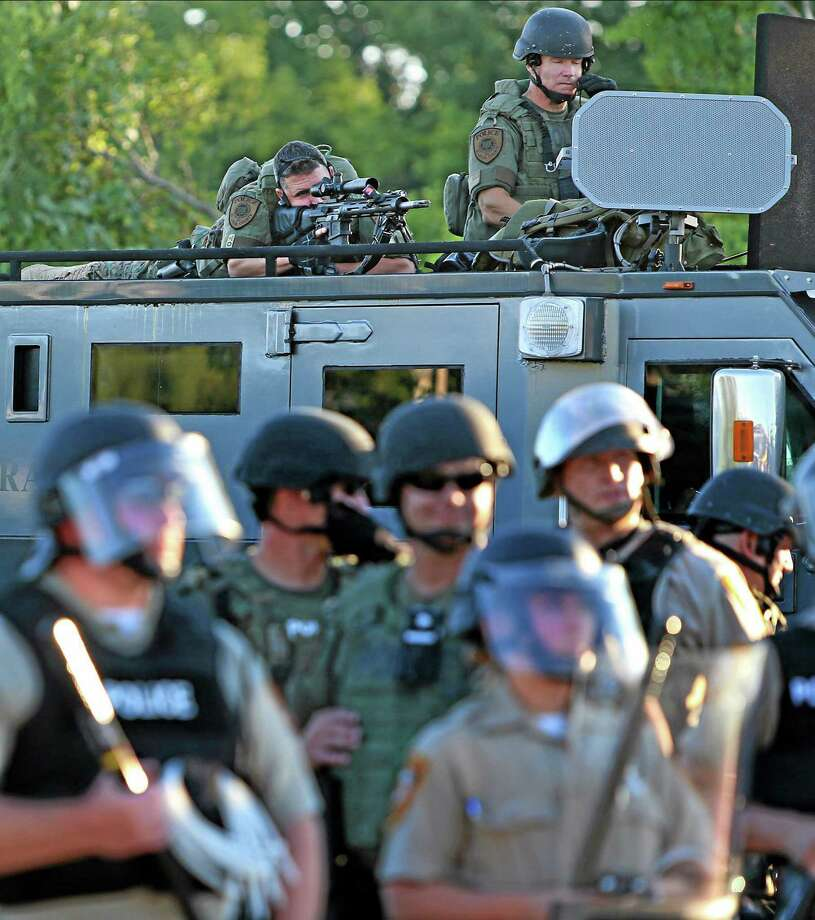 A police sharp shooter keeps an eye on protesters along W. Florissant Avenue on Tuesday, Aug. 12, 2014 near the QuikTrip that was burned down a few days earlier in Ferguson. (AP Photo/St. Louis Post-Dispatch, David Carson) Photo: AP / St. Louis Post-Dispatch