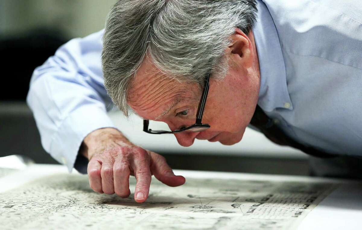 In this photo taken on Dec. 3, 2015, Boston Public Library curator of maps Ronald Grim, who helped reclaim this rare map that was stolen from the library, looks closely at it, in Boston. The centuries-old map compiled by French explorer Samuel de Champlain and believed to be among dozens stolen more than a decade ago from the Boston Public Library has been recovered, library officials said Friday, Dec. 4.