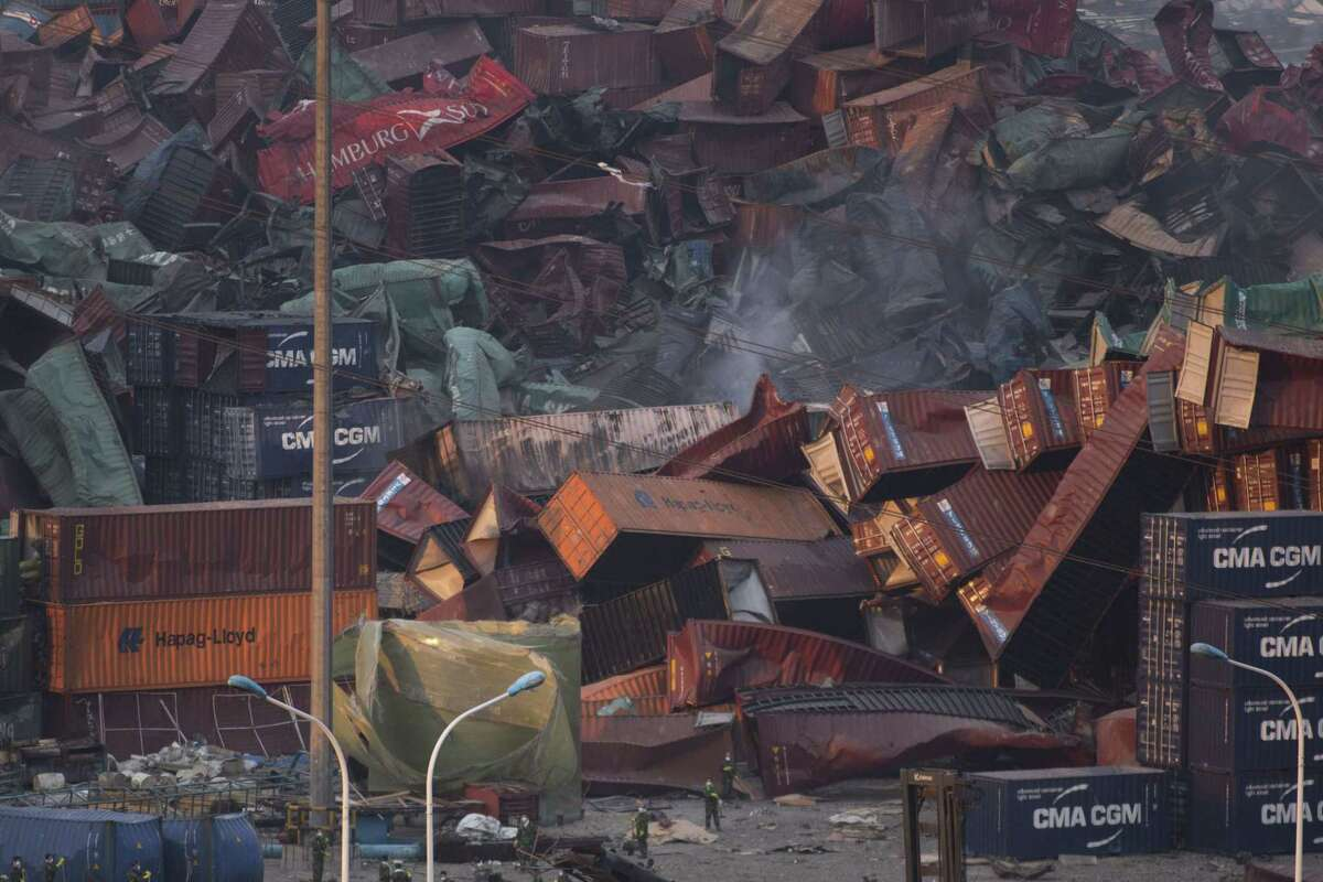 Workers sweep the area near deformed containers piled up after Wednesday's explosion in northeastern China's Tianjin municipality, Friday, Aug. 14, 2015. Rescuers pulled out a firefighter trapped for 32 hours after responding to a fire and huge explosions in the Chinese port city as authorities dealt Friday with a fire still smoldering amid potentially dangerous chemicals.