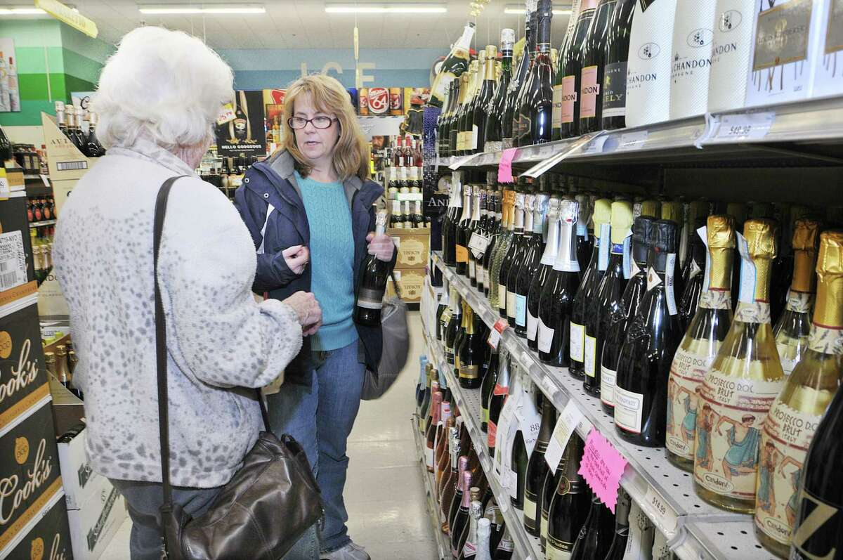 Customers choose a bottle of Ruffino Prosecco champagne at Connecticut Beverage Mart in Middletown to celebrate the new year in this file photo. Empire Wine & Liquor Superstore, based in New York, has applied for a zoning change to waive the 1,500-foot minimum distance between package stores in Middletown.