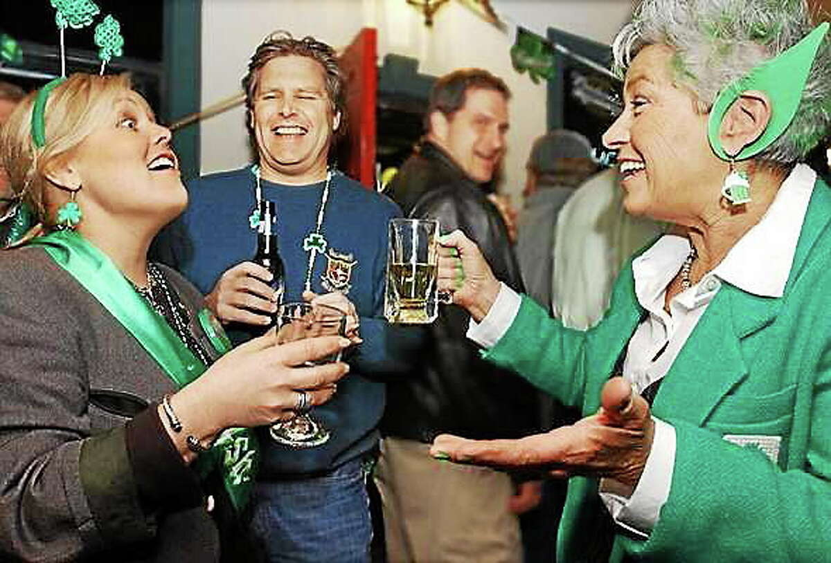 Catherine Avalone - The Middletown Press Dressed as an Irish leprechaun, Margo Chase-Wells, of Haddam, at right, swaps Irish jokes with Kelley Murphy Sadosky, of Higganum, and her brother, Terrence Murphy, of Middletown - all of whom are Irish - on St. Patrick's Day at the Claddagh House Irish Pub and Restaurant on Killingworth Road in Higganum.