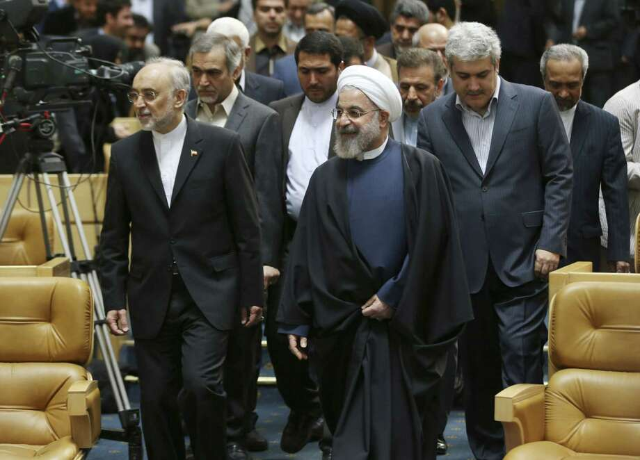 Iranian President Hassan Rouhani, center, arrives to attend a ceremony marking National Nuclear Technology Day, as he is accompanied by head of Iran's Atomic Energy Organization Ali Akbar Salehi, left, and Vice President for science and technology affairs Sorena Sattari, right, in Tehran, Iran, Thursday, April 9, 2015. Rouhani warned that Tehran will not sign on to a final nuclear deal with world powers unless it is predicated on the lifting of economic sanctions imposed on Iran over the controversial nuclear program. (AP Photo/Vahid Salemi) Photo: AP / AP