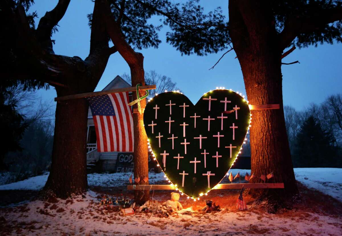 FILE - In this Dec. 14, 2013 file photo, a makeshift memorial with crosses for the victims of the Sandy Hook Elementary School shooting massacre stands outside a home in Newtown, Conn., on the one-year anniversary of the shootings.