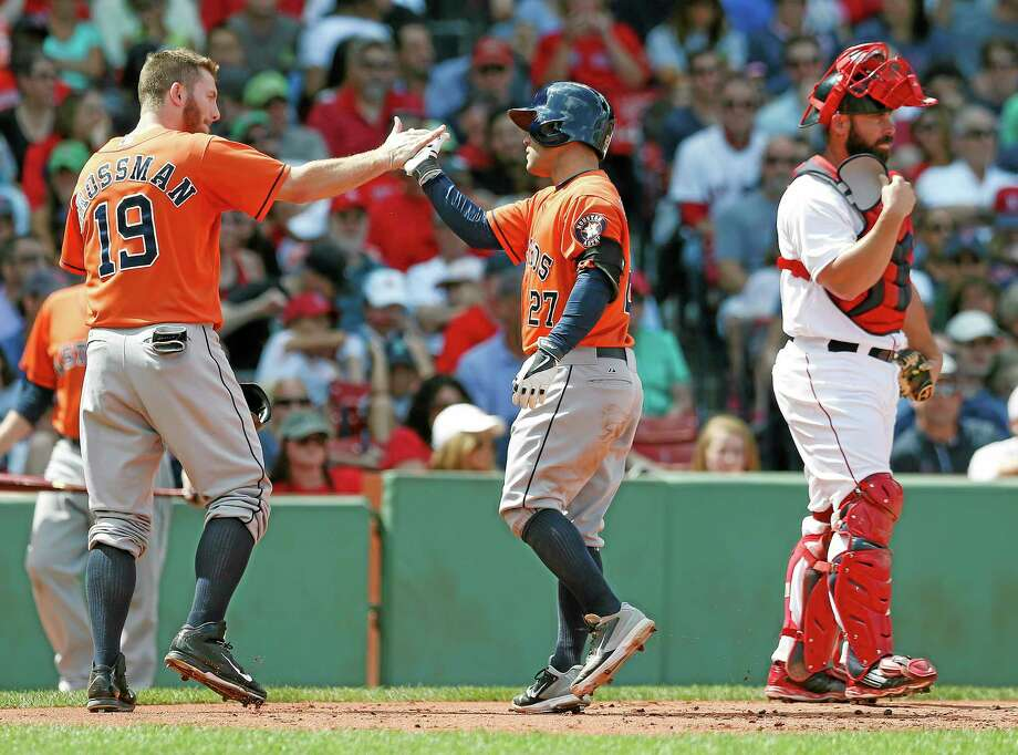 The Astros' Jose Altuve (27) celebrates his grand slam behind Red Sox catcher Dan Butler, right, in the second inning on Sunday. Photo: Michael Dwyer — The Associated Press  / AP
