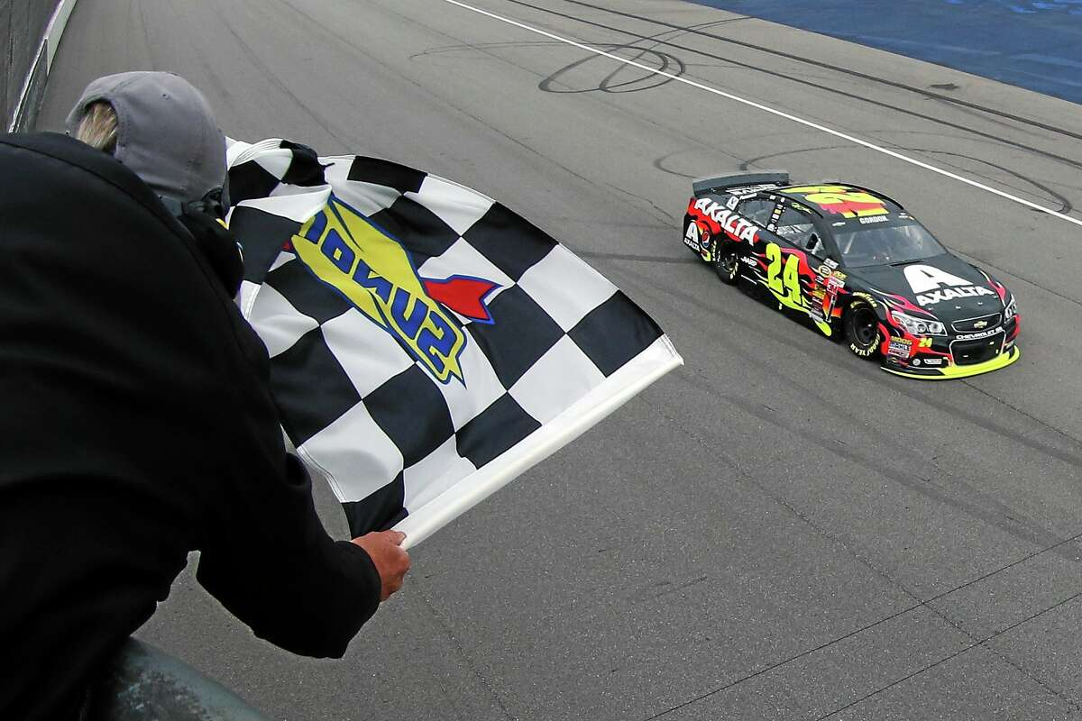 Jeff Gordon takes the checkered flag to win the Pure Michigan 400 at Michigan International Speedway on Sunday.