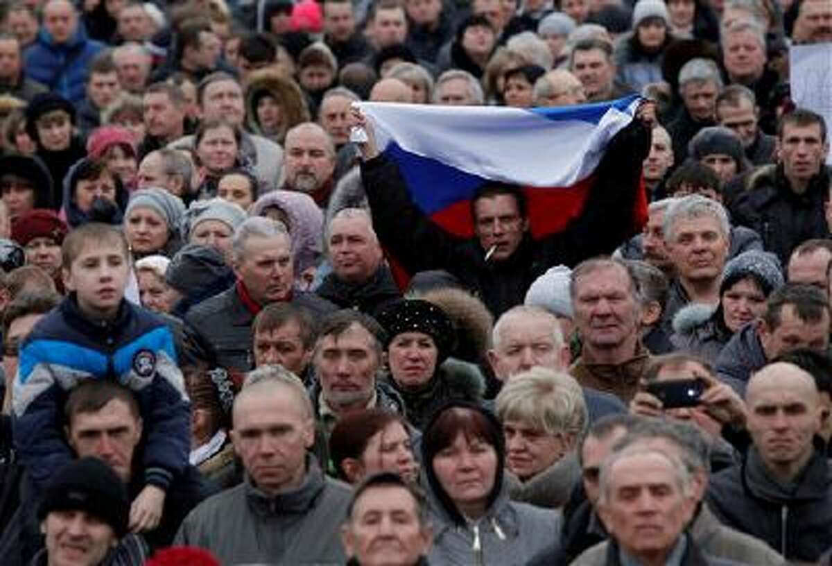 A man holds up a Russian flag as he attends a pro Russia rally at a central square in Donetsk, eastern Ukraine, Sunday, March 9, 2014. Following an extraordinary meeting of the Ukrainian government, Prime Minister Arseniy Yatsenyuk announced he would be flying later this week to the United States for high-level talks on
