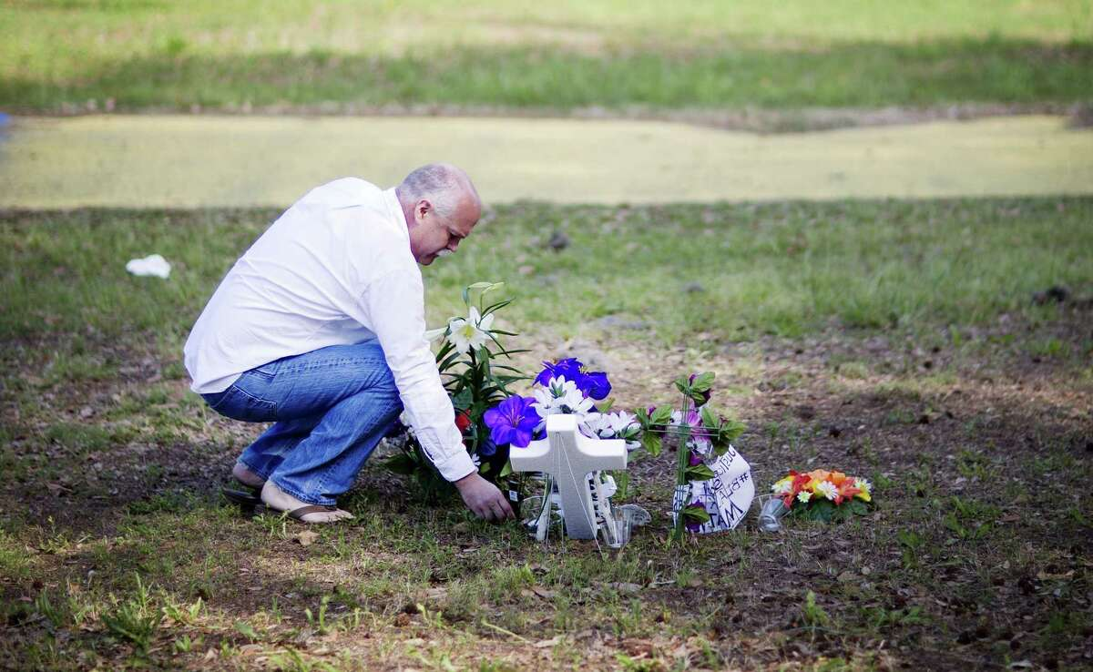 Jeffrey Spell, of Charleston, S.C., places flowers on Thursday at the scene where Walter Scott was killed by a North Charleston police officer Saturday after a traffic stop in North Charleston, S.C.