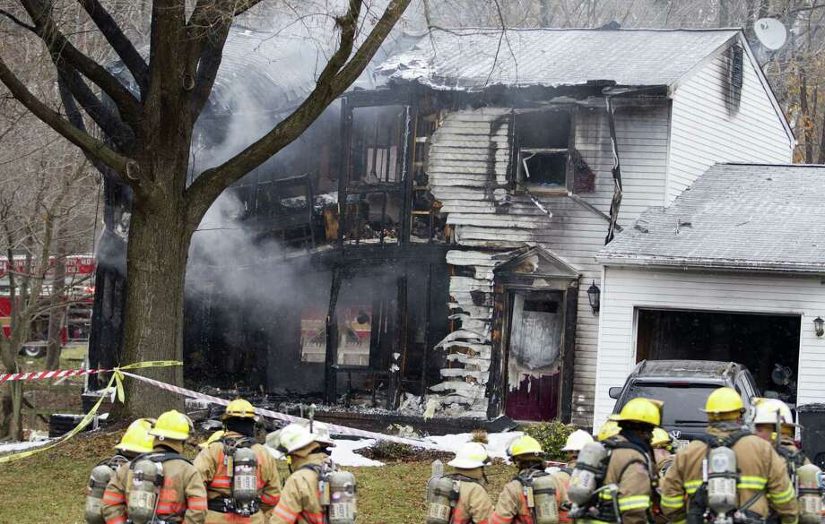 Firefighters stand outside a house in Gaithersbug, Md., Monday, Dec. 8, 2014, where a small plane crashed. A small, private jet has crashed into a house in Maryland's Montgomery County, and a fire official says at least three people on board were killed. (AP Photo/Jose Luis Magana) Photo: AP / FR159526 AP