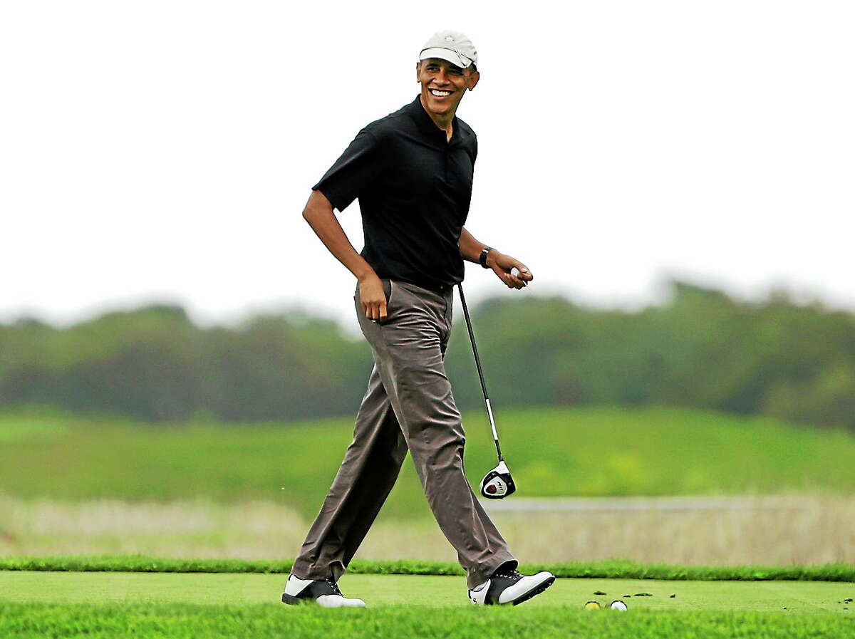 This Aug. 12, 2013 photo shows President Barack Obama as he steps onto a tee while golfing at Vineyard Golf Club in Edgartown, Mass., on the island of Martha's Vineyard, during his vacation.