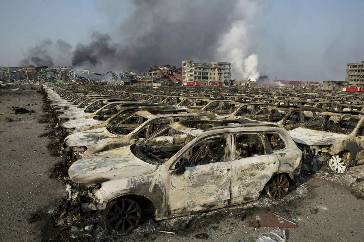Smoke billows from the site of an explosion that reduced a parking lot filled with new cars to charred remains at a warehouse in northeastern China's Tianjin municipality on Aug. 13, 2015. Huge, fiery blasts at a warehouse for hazardous chemicals killed many people and turned nearby buildings into skeletal shells in the Chinese port of Tianjin, raising questions Thursday about whether the materials had been properly stored.