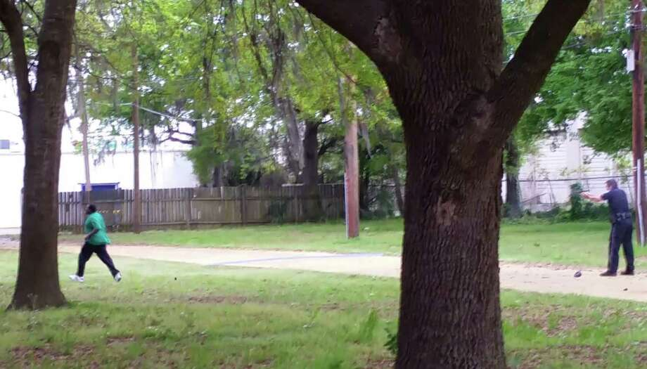 In this April 4, 2015, frame from video provided by Attorney L. Chris Stewart representing the family of Walter Lamer Scott, Scott appears to be running away from City Patrolman Michael Thomas Slager, right, in North Charleston, S.C. Slager was charged with murder Tuesday, hours after law enforcement officials viewed the dramatic video that appears to show Slager shooting a fleeing Scott several times in the back. Photo: (AP Photo/Courtesy Of L. Chris Stewart) / L. Chris Stewart