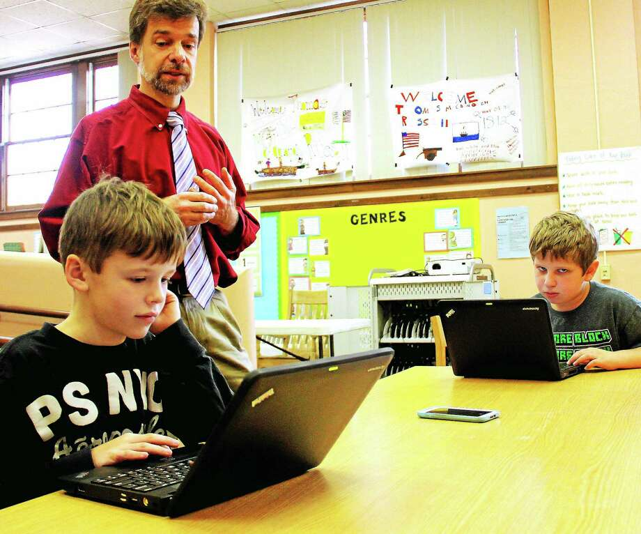 Macdonough Elementary School fourth-graders Ryan Gartner and James Mayer, both coding club members, work with Middletown grade school's science, technology, engineering and math teacher teacher John Ferrero in the library recently. Photo: Kathleen Schassler — The Middletown Press  / Kathleen Schassler All Rights