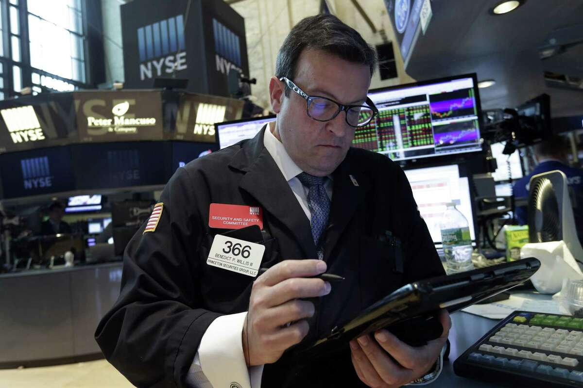 Trader Bebedict Willis works on the floor of the New York Stock Exchange on Aug. 12, 2015. Another drop in China's currency sent global markets mostly lower on Wednesday as the move raised worries about the world's second-largest economy, but U.S. stocks recovered most of their losses in late trading.