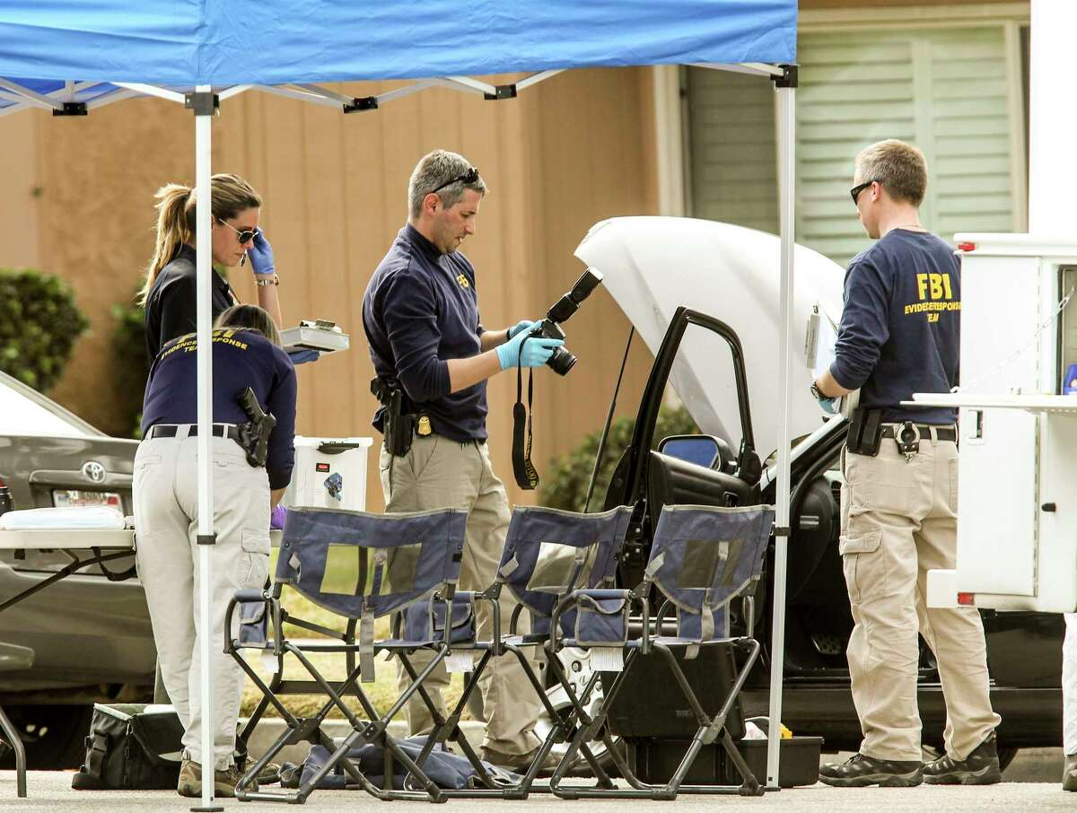 FBI agents investigate a car near a home in connection to Wednesday's shootings in San Bernardino Thursday in Redlands, Calif.