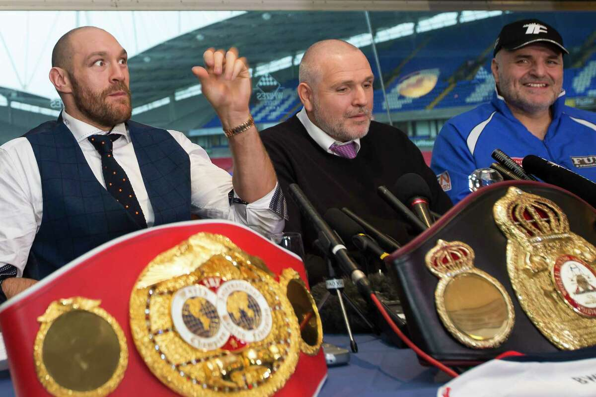 Newly crowned heavyweight world boxing champion Tyson Fury, left, getures as he sits alongside his uncle and trainer Peter Fury, center, and his father John Fury at a media day Monday in Bolton, England.