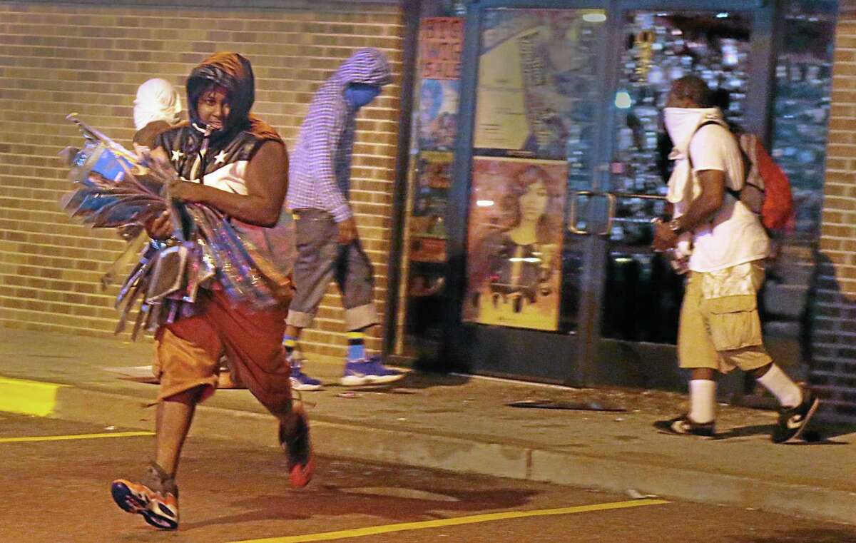 A looter escapes with items from Feel Beauty Supply on West Florissant Avenue in Ferguson early Saturday, Aug. 16, 2014, after protestors clashed with police. (AP Photo/St. Louis Post-Dispatch, Robert Cohen)