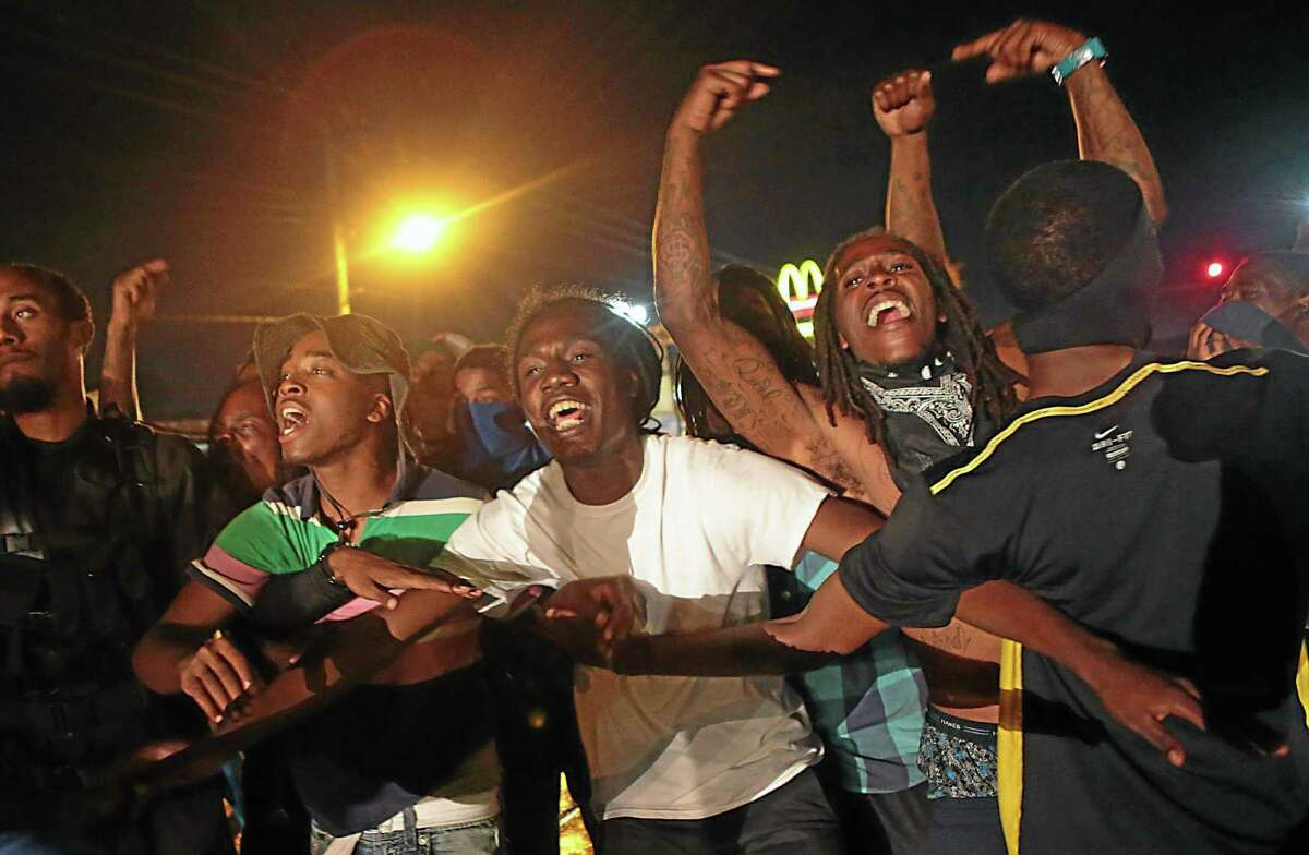 Protestors stand in the middle of West Florissant Avenue in Ferguson, refusing to leave despite police orders early Saturday, Aug. 16, 2014. (AP Photo/St. Louis Post-Dispatch, Robert Cohen)