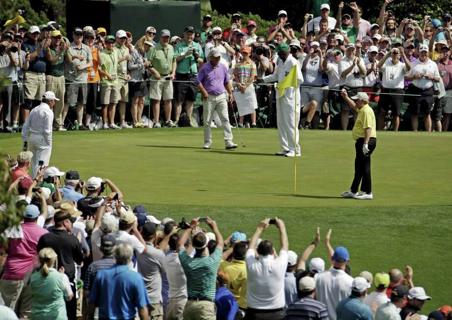 Jack Nicklaus, right, holds up his ball after a hole-in-one on the fourth hole during the par-3 contest at the Masters on Wednesday in Augusta, Ga. Photo: Charlie Riedel — The Associated Press  / AP