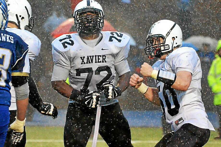 Xavier's Chidi Broderick, left, and Colin Morris celebrate after sacking Newtown quarterback Jacob Burden in Xavier's 13-7 win over Newtown. Playoff loss a tough one Photo: Pete Paguaga — New Haven Register