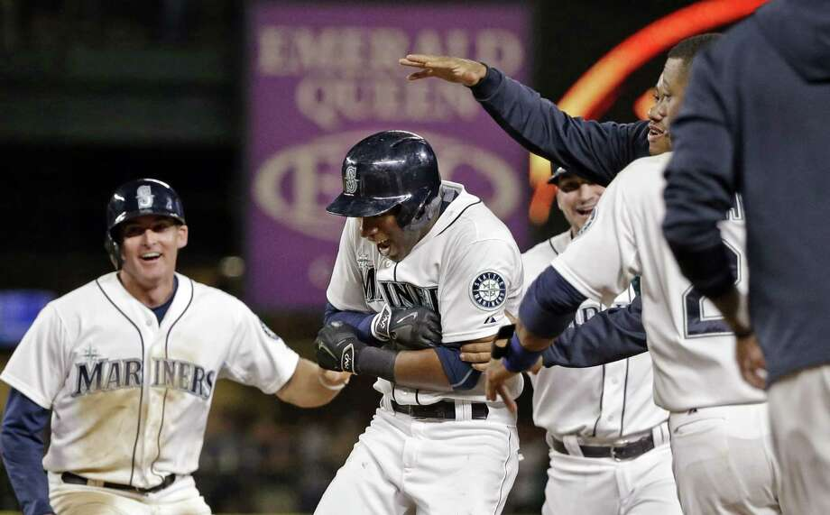 The Mariners' Austin Jackson, center, is mobbed by teammates after driving in the winning run against the Baltimore Orioles in the 10th inning Tuesday in Seattle. Photo: Elaine Thompson — The Associated Press  / AP
