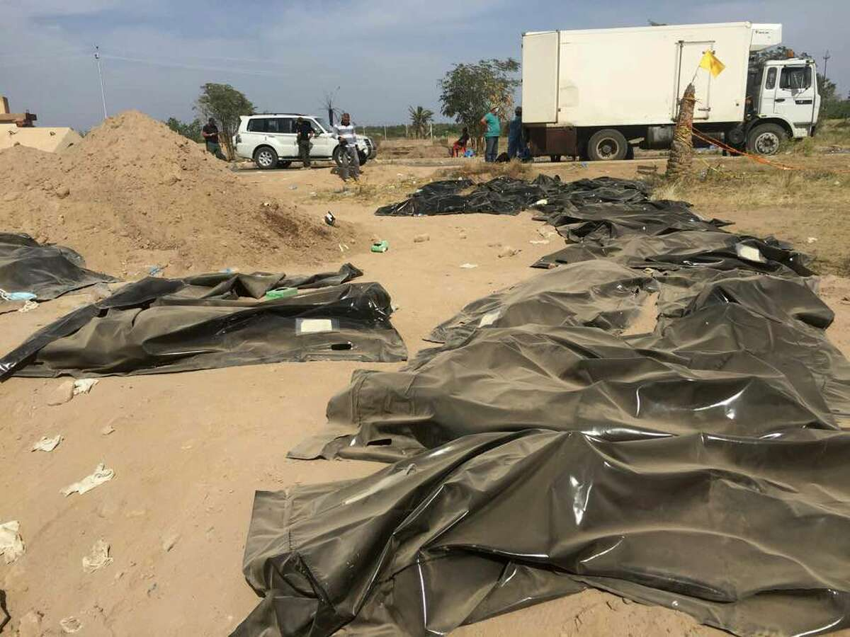 This April 7, 2015 photo shows human remains from a mass grave, believed to contain the bodies of Iraqi soldiers killed by Islamic State group militants when they overran Camp Speicher military base last June, in Tikrit, Iraq.