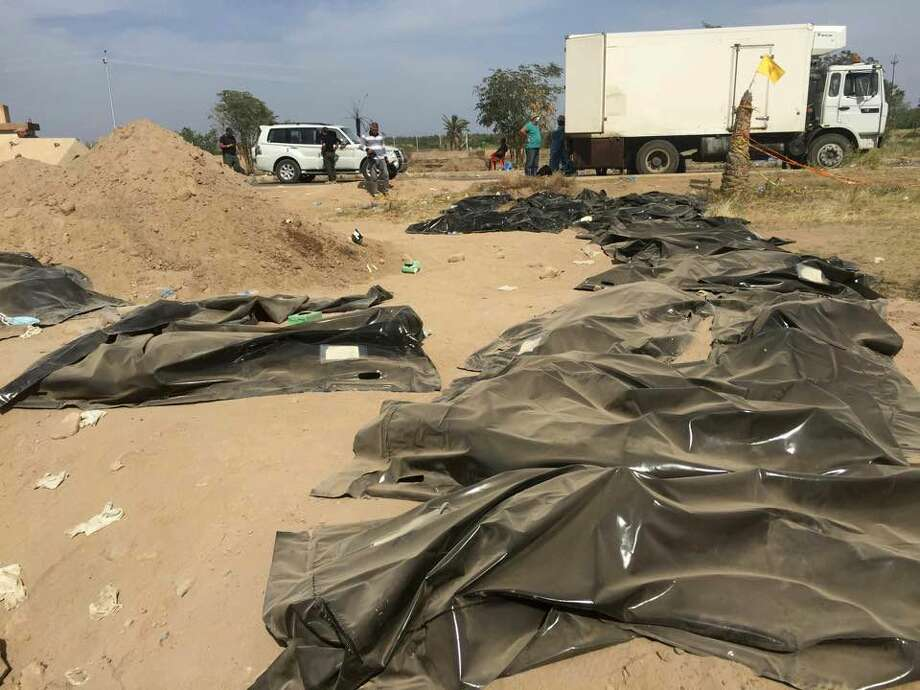 This April 7, 2015 photo shows human remains from a mass grave, believed to contain the bodies of Iraqi soldiers killed by Islamic State group militants when they overran Camp Speicher military base last June, in Tikrit, Iraq. Photo: AP Photo  / AP