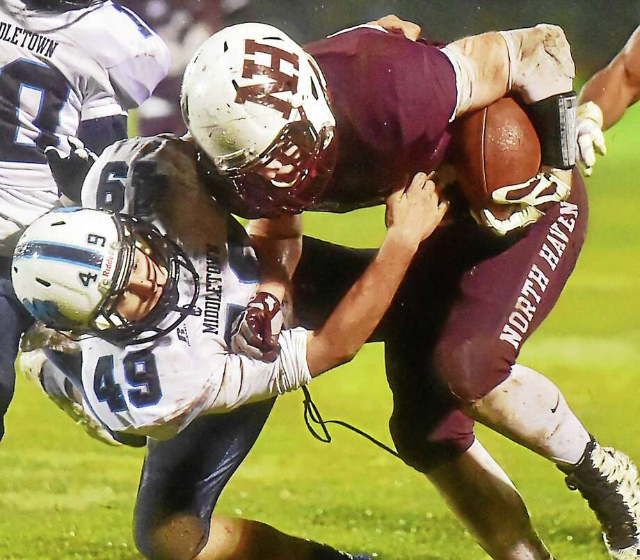 Middletown's Michael Souza tackles North Haven's Conner Suraci in a Blue Dragon loss, 48-13, Tuesday in the Class L state football quarterfinal game. Photo: Catherine Avalone/The Middletown Press / Catherine Avalone/New Haven Register