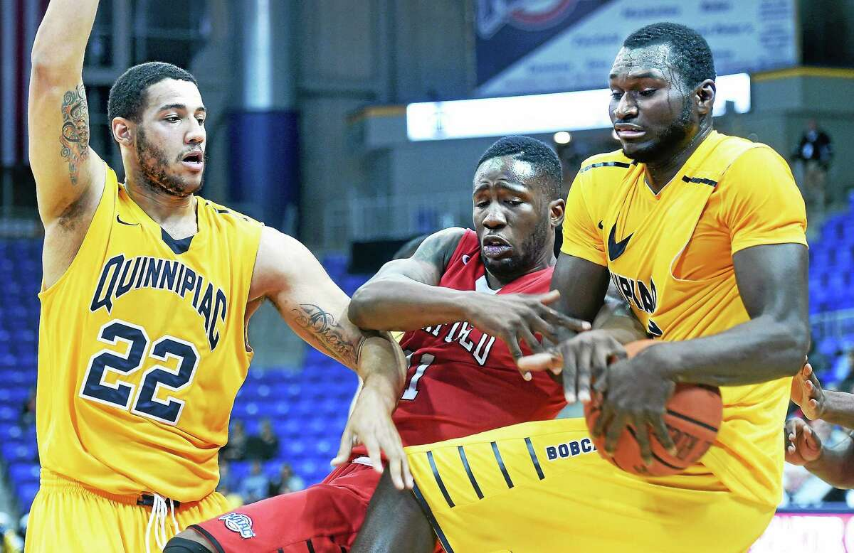 (Arnold Gold-New Haven Register) Justin Harris (left) and Ousmane Drame (right) of Quinnipiac University fight for a rebound with Amadou Sidibe (center) of Fairfield University in the first half on 12/7/2014.