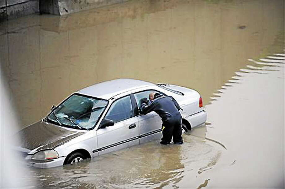 A police diver checks a flooded vehicle for any occupants along a flooded stretch of I-696 at the Warren, Mich. city limits Tuesday morning, Aug. 12, 2014. Warren Mayor James Fouts said roughly 1,000 vehicles had been abandoned in floodwaters in the suburb where many roads were closed after 5.2 inches of rain fell Monday. (AP Photo/Detroit News, David Coates)  DETROIT FREE PRESS OUT; HUFFINGTON POST OUT Photo: AP / Detroit News
