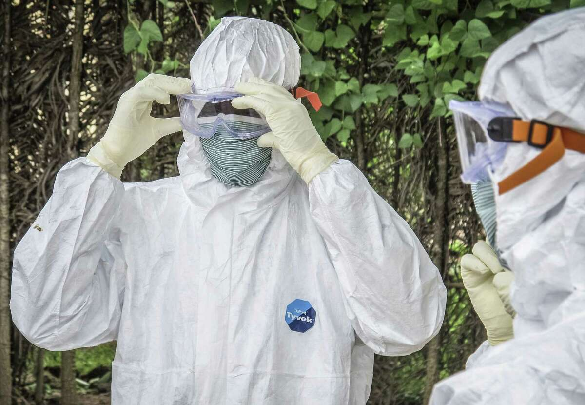 In this Tuesday, Oct. 21, 2014 photo, health workers wear protective clothing before entering the house of a person suspected to have died of Ebola virus in Port loko Community situated on the outskirts of Freetown, Sierra Leone.