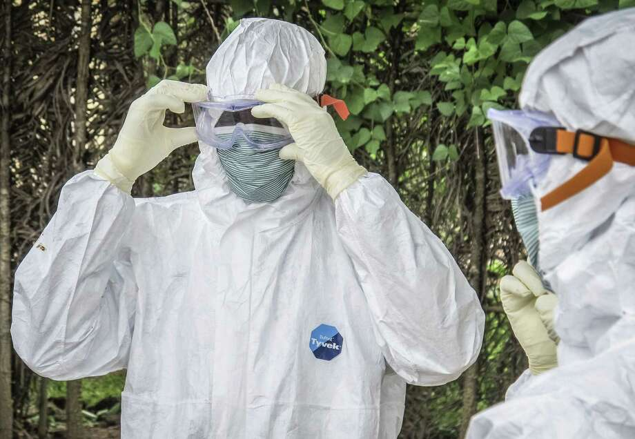 In this Tuesday, Oct. 21, 2014 photo, health workers wear protective clothing before entering the house of a person suspected to have died of Ebola virus in Port loko Community situated on the outskirts of Freetown, Sierra Leone. Photo: AP Photo/Michael Duff, File  / AP
