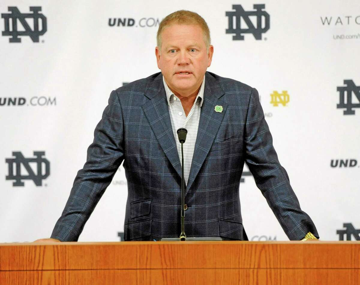 "Notre Dame football coach Brian Kelly talks to the media at the beginning of fall practice on Aug. 1 in South Bend, Ind. Notre Dame says it is investigating ""suspected academic dishonesty"" involving several students, including four members of the football team. The school released a statement Friday saying it has notified the NCAA and that because of potential NCAA violations the four players are being held out of practice and completion until the conclusion of the investigation and the university honor code process."