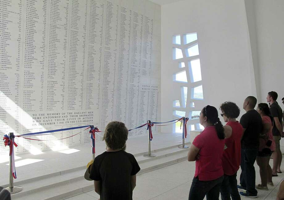 This Nov. 21, 2014 photo shows visitors looking at a wall inscribed with the names of the USS Arizona's fallen at a memorial for the sunken battleship in Pearl Harbor, Hawaii. Photo: AP Photo/Audrey McAvoy  / AP
