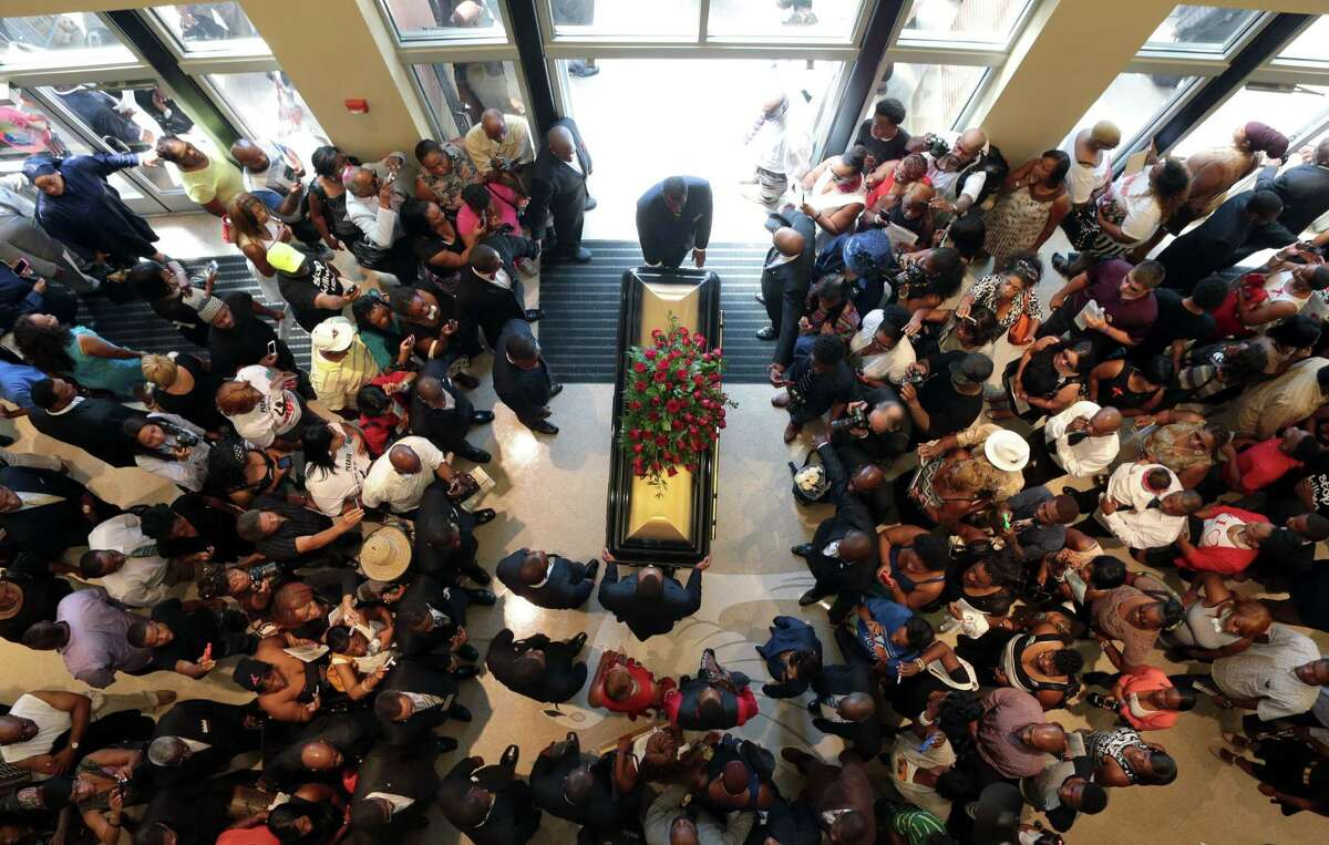 In this Aug. 25, 2014 photo the casket containing the body of Michael Brown is surrounded people gathered to say goodbye as it leaves Friendly Temple Missionary Baptist Church in St. Louis, Mo.