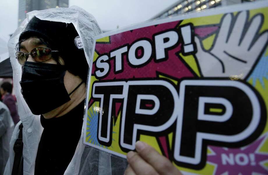 In this April 22, 2014, file photo, a protester holds a placard during a rally against the Trans-Pacific Partnership in Tokyo. The United States is negotiating the ambitious trade agreement with 11 other Pacific Rim countries that's meant to ease barriers to fast-growing Asia-Pacific markets and streamline customs rules. Photo: AP File Photo  / AP