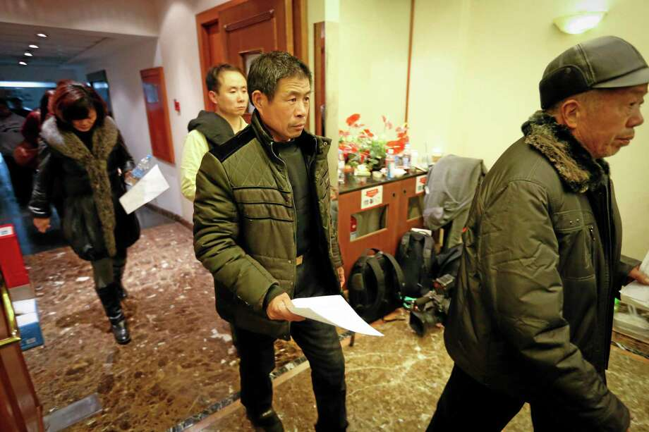 Chinese relatives of passengers aboard a missing Malaysia Airlines plane are leaving a hotel for relatives or friends of passengers aboard the missing airplane to apply for a passport in Beijing, China Sunday, March 9, 2014. Planes and ships from across Asia resumed the hunt Sunday for a Malaysian jetliner missing with 239 people on board for more than 24 hours, while Malaysian aviation authorities investigated how two passengers were apparently able to get on the aircraft using stolen passports. (AP Photo/Vincent Thian) Photo: AP / AP
