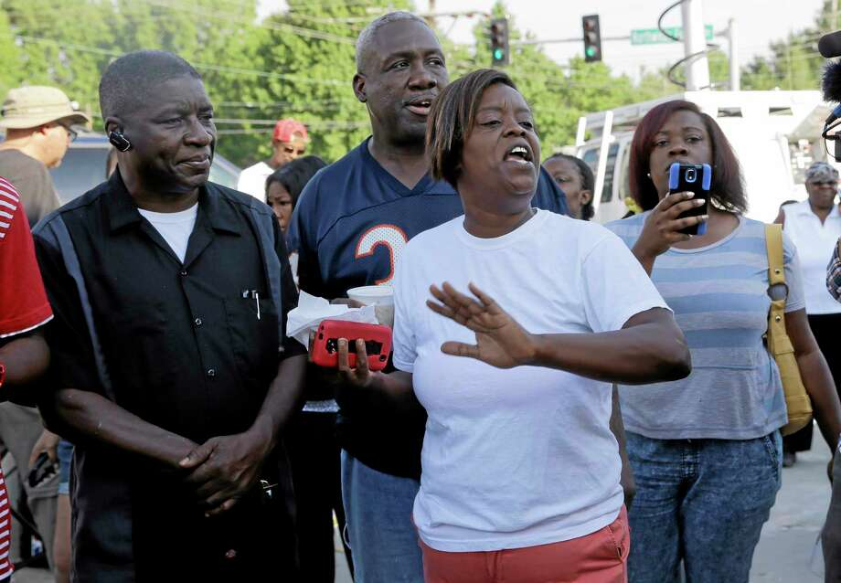 People react after Ferguson Police Chief Thomas Jackson releases the name of the the officer accused of fatally shooting Michael Brown, an unarmed black teenager, Friday, Aug. 15, 2014, in Ferguson, Mo. The officer's name is Darren Wilson, a six-year veteran of the force. Photo: Jeff Roberson — The Associated Press  / AP