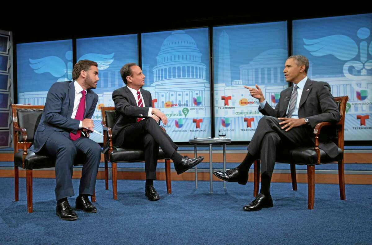 President Barack Obama talks with television hosts Jose Diaz Balart, center, and Enrique Acevedo, left, during a town hall event on the importance of the benefits of the Affordable Care Act for Hispanic community, Thursday, March 6, 2014, at the Newseum in Washington. (AP Photo/Pablo Martinez Monsivais)