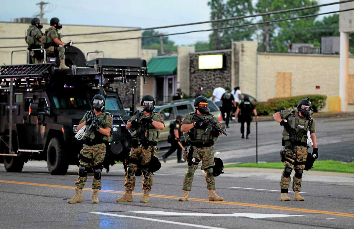 Police wearing riot gear try to disperse a crowd Monday, Aug. 11, 2014, in Ferguson, Mo.