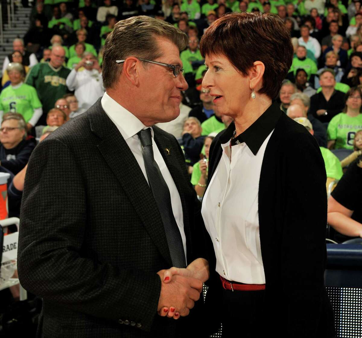 Notre Dame coach Muffet McGraw, right, and UConn coach Geno Auriemma talk before Saturday's game in South Bend, Ind.