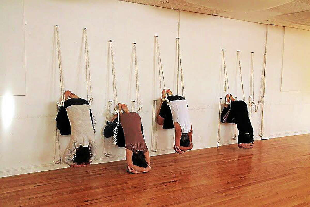 Submitted photo. Guests are shown practicing Iyengar yoga at Yoga in Middletown. The practice places an emphasis on detail, precision and alignment in the performance of posture and breath control using wall ropes. Such will be offered during a series of workshops at the 438 Main Street studio starting this month.