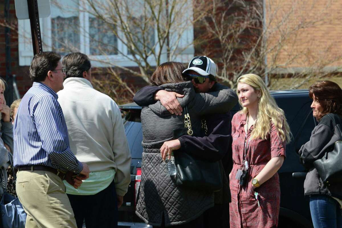 People gather across the street from the home where the bodies of an elderly couple were found Monday, in Elmwood Park, N.J.