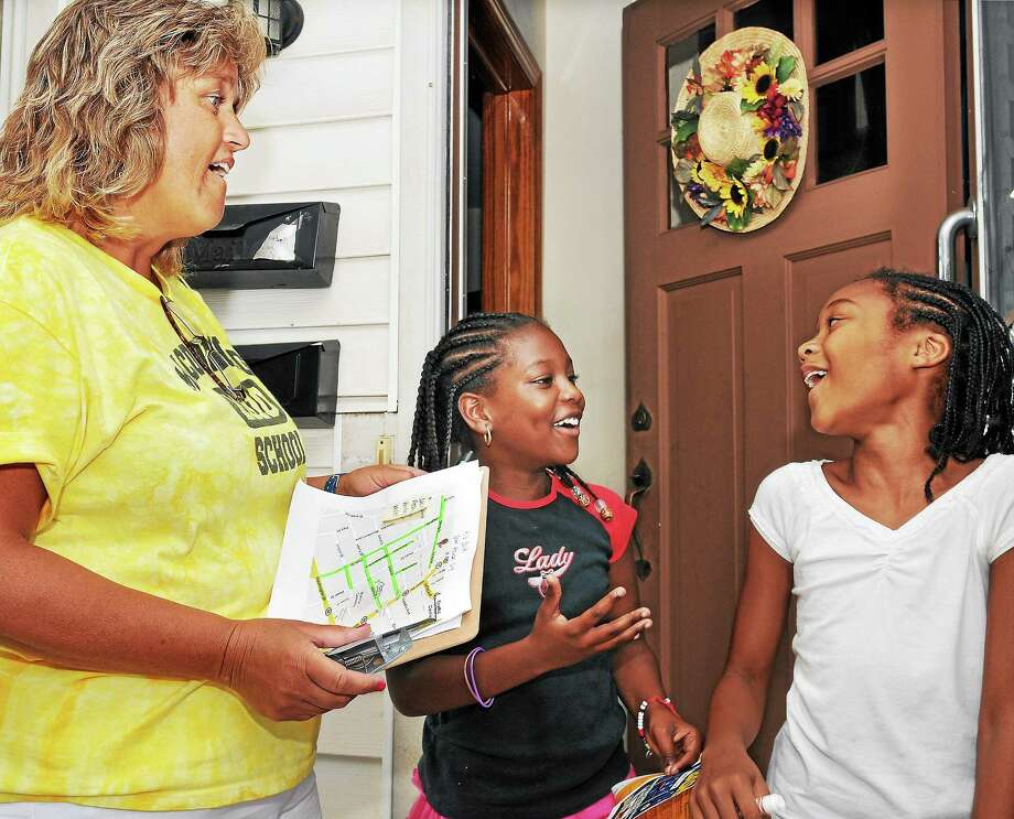 Lenicia Collins, 8, and Nasharie Davis, 9, are surprised to see Joanne Jukins, a second-grade teacher from Macdonough School visit their home on Spring Street in this 2010 file photo. Photo: Catherine Avalone - The Middletown Press File Photo  / TheMiddletownPress
