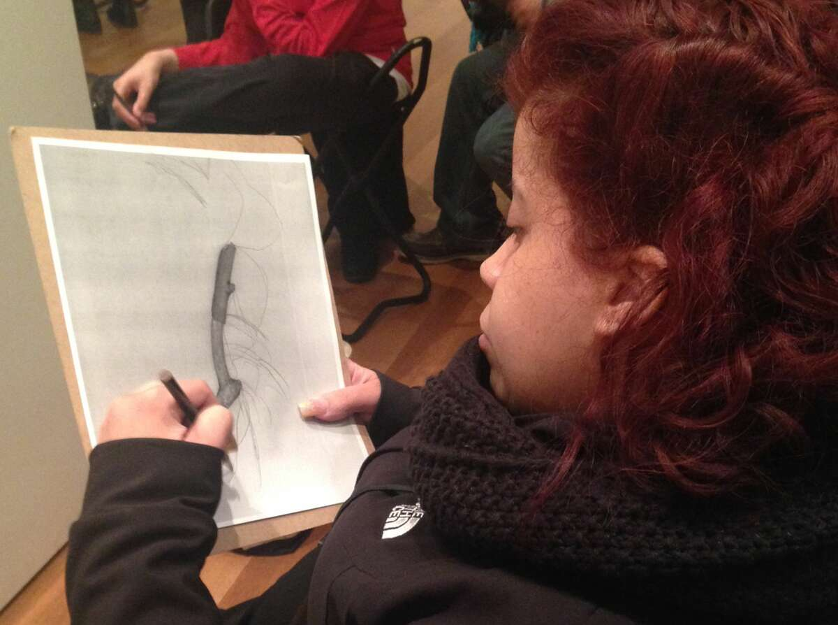 """In this March 22, 2015 photo, Luz Cantres works on a drawing at the Museum of Modern Art in New York after viewing a sculpture by French artist Jean Dubuffet. Cantres was participating in """"Create Ability,"""" a program for individuals with learning and developmental disabilities."""