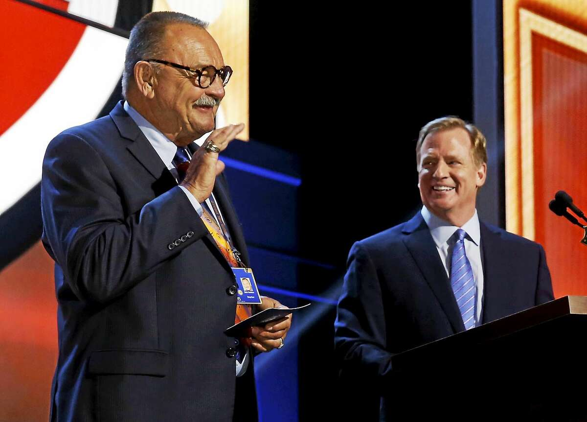 NFL Hall of Famer Dick Butkus, left, waves as NFL commissioner Roger Goodell introduces him during the 2015 NFL Draft on May 1 in Chicago.